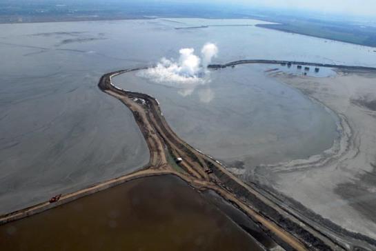 Foto udara tanggul cincin yang mengelilingi pusat semburan lumpur panas Lapindo, Porong Sidoarjo, Sabtu (14/2).